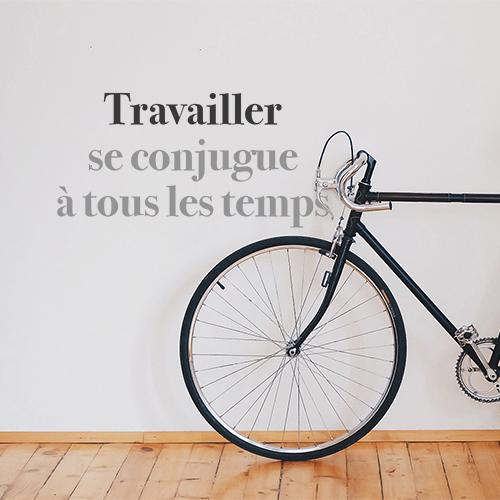Sticker autocollant mural citation travailler se conjugue collé au mur du couloir derrière le vélo