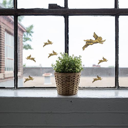 Stickers angelots collés sur une fenêtre vintage devant une plante verte