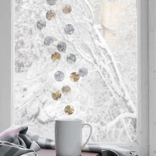 Stickers boules de verre argent et dorés collés sur une fenêtre