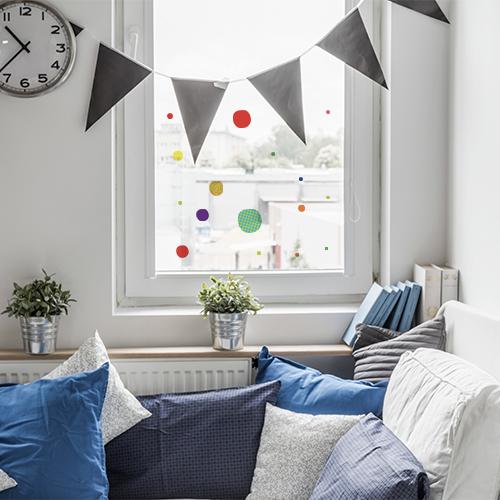 Décorations électrostatiques pour vitres ronds carrés colorés sur une fenêtre blanche.