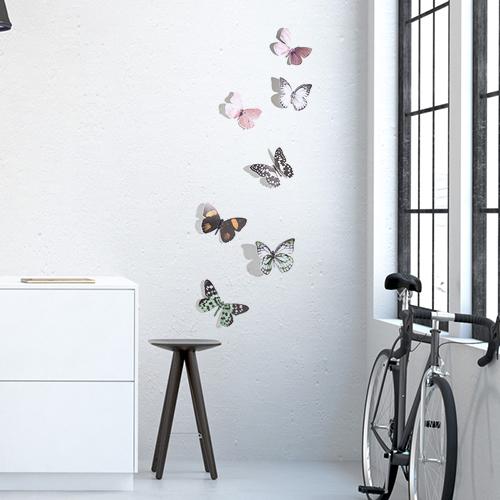 Sticker adhésif Papillons réalistes sur un mur blanc avec un vélo et une table basse