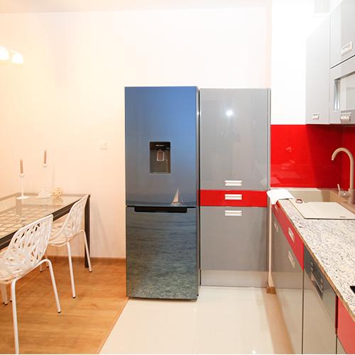 Adhésif sticker autocllant sur grand frigo de taille classique dans cuisine rouge et grise moderne