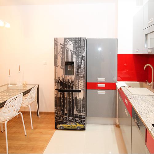 Sticker New York posé sur un frigo dans une cuisine au ton rouge