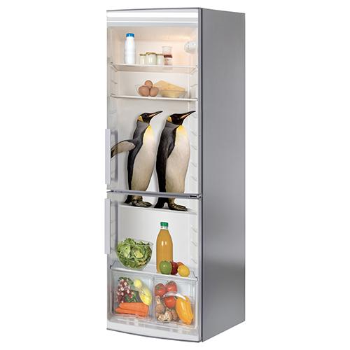 Sticker autocollant pinguin collé sur la porte d'un grand frigo classique
