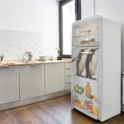 Sticker décoratif pinguin dans un frigo collé sur la porte d'un grand frigo