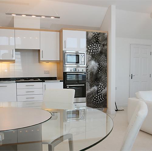Cuisine moderne et spacieuse possédant un grand frigo orné d'un sticker autocollant duvet de plumes