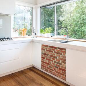 Cuisine classique avec un sticker décoratif adhésif briques rouges collé sur le meuble de la cuisine sous l'évier