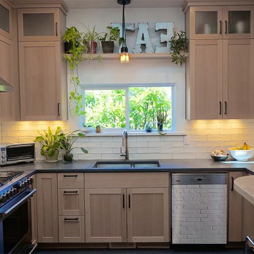 Cuisine moderne avec des meubles en blois et un lave vaisselle décoré avec un sticker imitation brique blanche