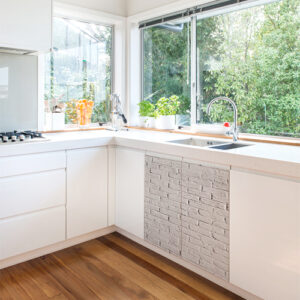 Cuisine classique blanche avec un sticker déco imitation brique collé sur le meuble sous l'évier
