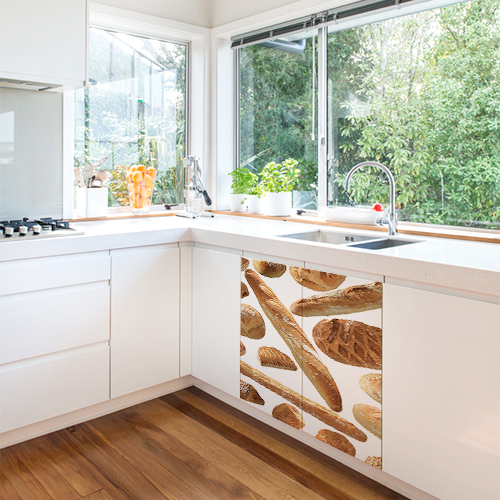 Cuisine originale blanche avec un sticker autocollant boulangerie collé sur les portes du meuble sous l'évier