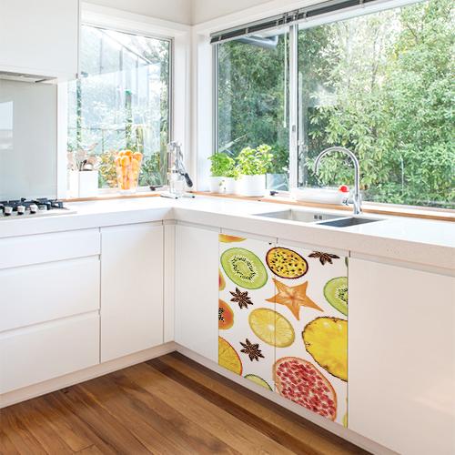 Placard sous l'évier d'une cuisine blanche orné d'un sticker autocollant FRUITS EXOTIQUES