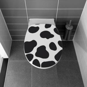 Salle de bain avec des WC ornés d'un motif autocollant taches de vaches
