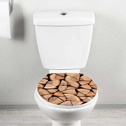 Siège de toilette décoré avec un sticker adhésif buches coupées