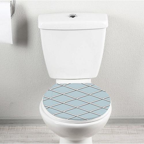 Salle de toilettes avec un sticker géométrique bleu et blanc collé sur les WC
