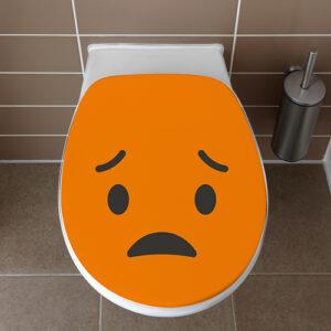 Abattant de WC avec un sticker déçu orange collé dessus