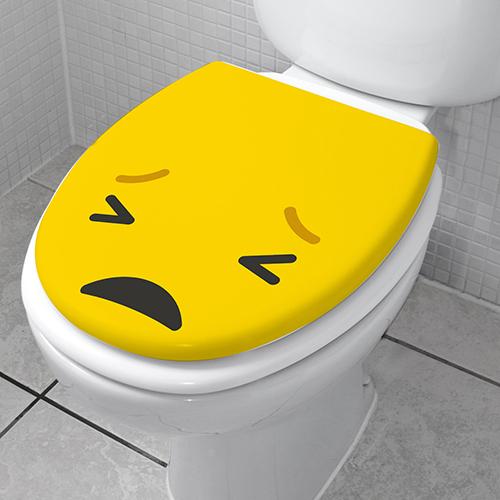 Salle de bain avec un WC orné d'un sticker Smiley pas content jaune