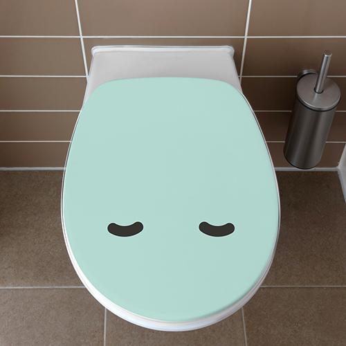 Abattant de toilettes avec un Smiley turquoise endormi collé sur l'abattant