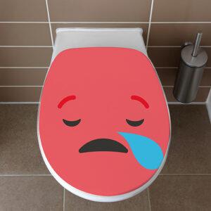 Abattant de WC orné d'un sticker de la gamme Smiley : le smiley triste rouge vu de dessus