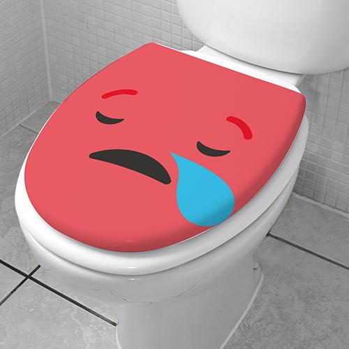 Smiley triste rouge collé sur un abattant de WC vu de 3/4