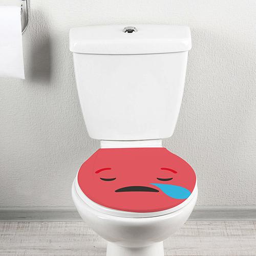 Sticker autocollant Smiley triste rouge collé sur un toilette blanc vu de face