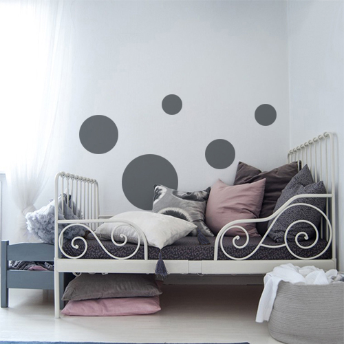 Autocollant décoratif rond gris foncé pour déco de mur blanc dans une chambre d'enfant