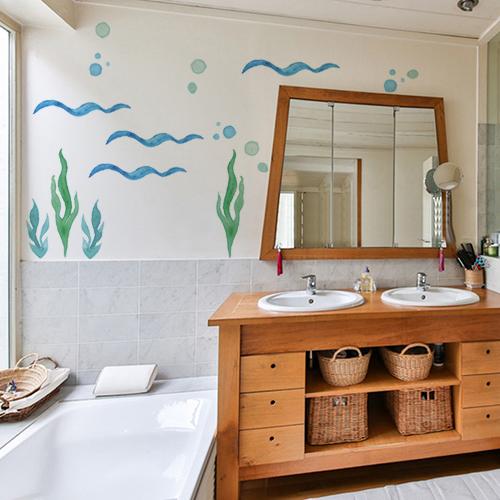 sticker algues en déco sur le mur d'une salle de bain avec des meubles en osier
