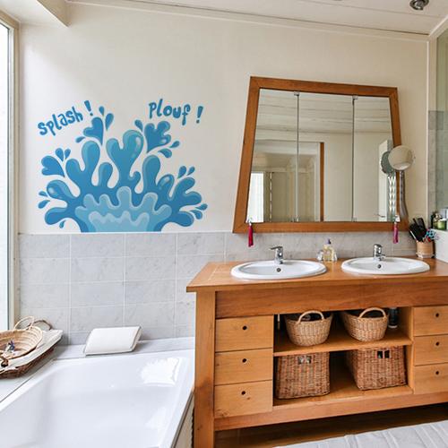 sticker plouf sur un mur de salle de bain lumineuse avec des meubles en osier