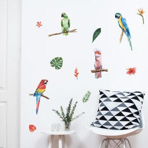 Jolis stickers muraux exotiques représentant des perroquets et autres éléement tropicaux posés sur un mur blanc dans un intérieur scandinave.