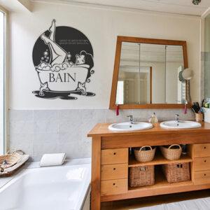 sticker décoratif bain citation et graphisme apposé sur les murs d'une salle de bain avec les meubles en osier