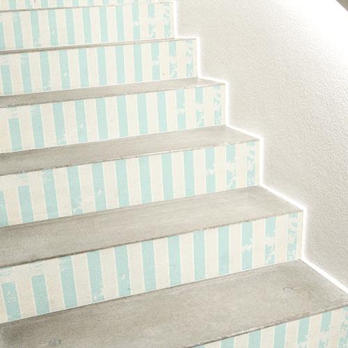 Escaliers en béton blanc avec des stickers cabane de plage collés sur les contremarches