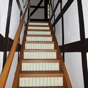 Contremarches classiques dans une maison en bois avec des stickers motif cabine de plage vintage collés dessus.