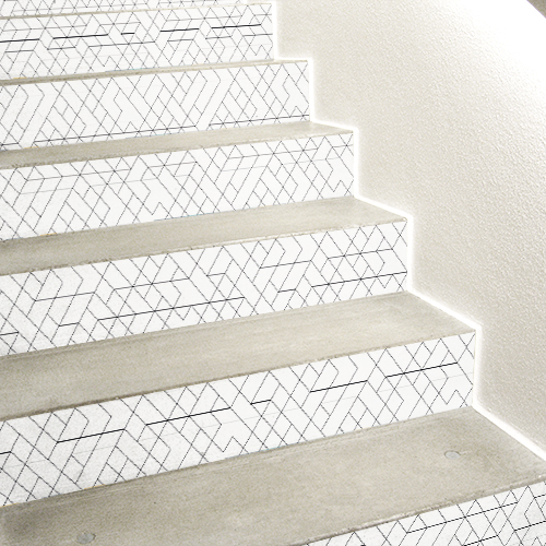 Stickers décoratifs blancs avec des motifs noirs collés sur des contremarches d'escaliers en béton