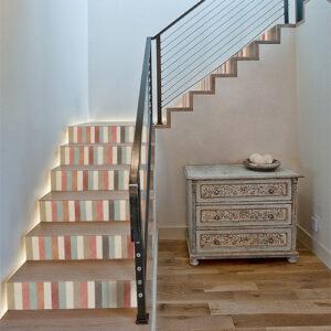 Escalier standard en bois avec des bandes multicolores collées sur les contremarches