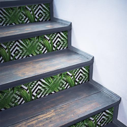 Escaliers en bois noirs dont les marches sont décorés par des stickers autocollants décoratifs motif fougères sur fond noir et blanc