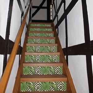 Fougères vertes sur fond blanc et noir collées sur des contremarches d'escalier classique.