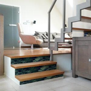Fougères vertes foncé sur fond noir collées sur des escaliers en bois