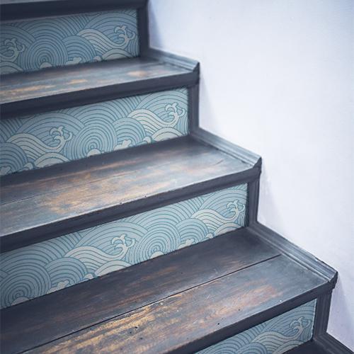 Vagues dessinées avec un style asiatique décorant les contremarches d'un escalier en bois noir