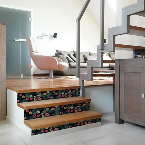 Escalier moderne en bois avec des fleurs multicolores collées sur les contremarches