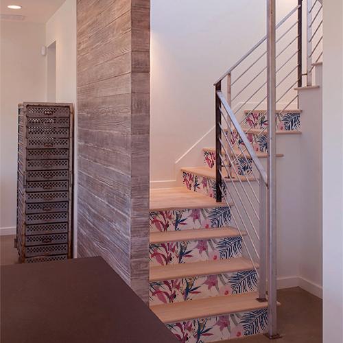 Stickers autocollants représentant des plantes exotiques et un oiseau collés sur plusieurs marches d'un escalier en bois.