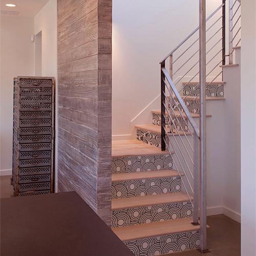 Stickers décoratifs représentant des cercles blancs collés sur les contremarches d'escaliers en bois dans une maison moderne