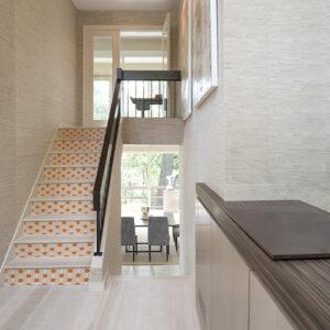 Maison moderne et luxueuse avec des stickers représentant des écailels de poissons stylisés oranges collés sur les contremarches
