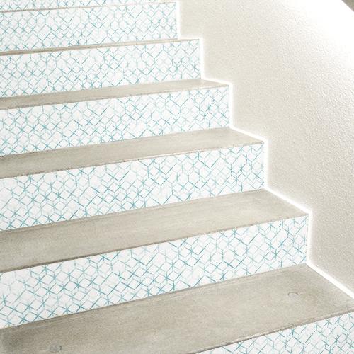 Stickers 3D représentant une ruche d'abeille blanc collé sur les contremarches d'un escalier en béton blanc