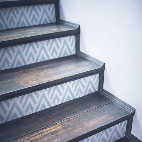 Stickers décoratifs chevrons bleus clair et blancs posés sur des escaliers noirs en bois