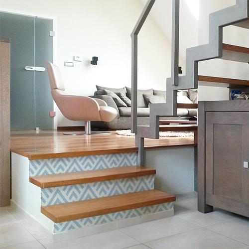 Escaliers modernes en bois avec des stickers bleus et blancs représentant des motifs géométriques collés sur les contremarches
