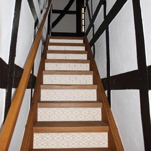 Maison tradtionnelle en bois avec des stickers crèmes et noirs représentant des hexagones collés sur els escaliers