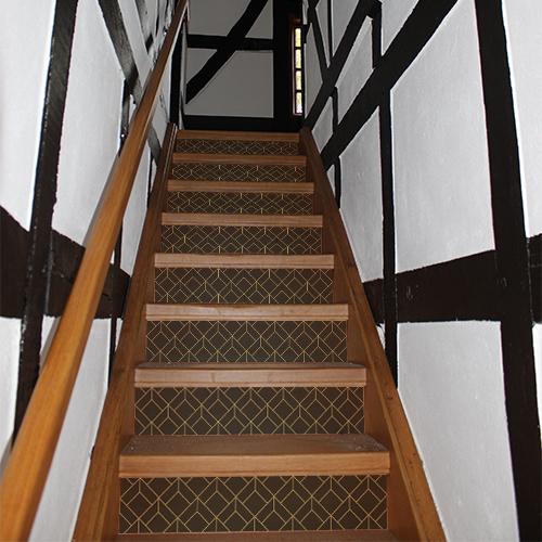 Maison traditionnelle en bois avec des escaliers décorés avec des stickers adhésifs décoratifs noirs et or représentant des carrés en 3D