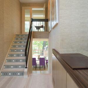 Maison moderne dont les escaliers en bois sont décorés par des stickers autocollants noirs représentant des formes géométriques