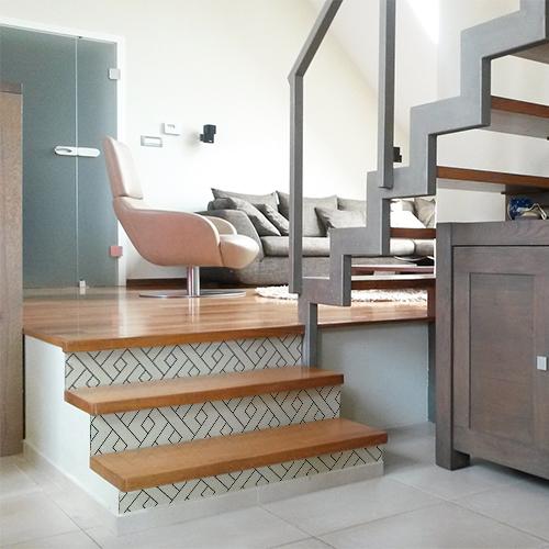Stickers adhésifs décoratifs représentant des formes géométriques blanches collés sur des escaliers en bois