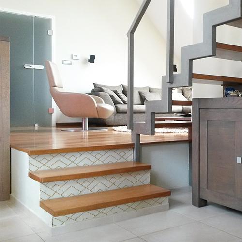Maison moderne avec des escaliers décorés par une mosaïque ressemblant à des pyramides blanches et or.