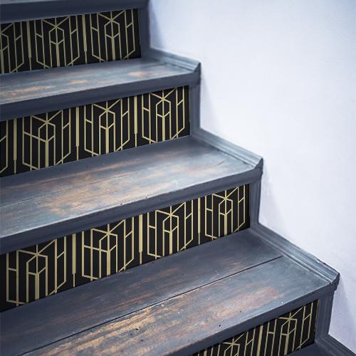 Escaliers en bois noir avec des stickers autocollants représentant des formes géométriques noir et blanches collés sur les contremarches